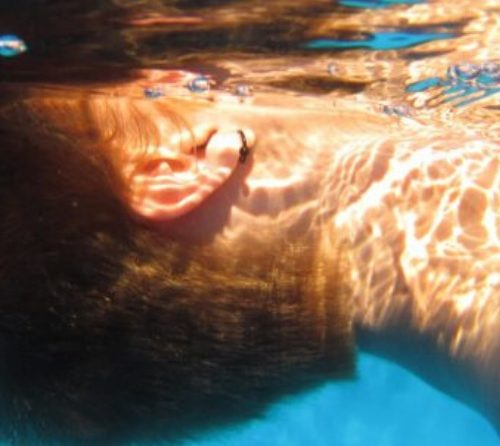 An underwater photo of someone floating on the surface.