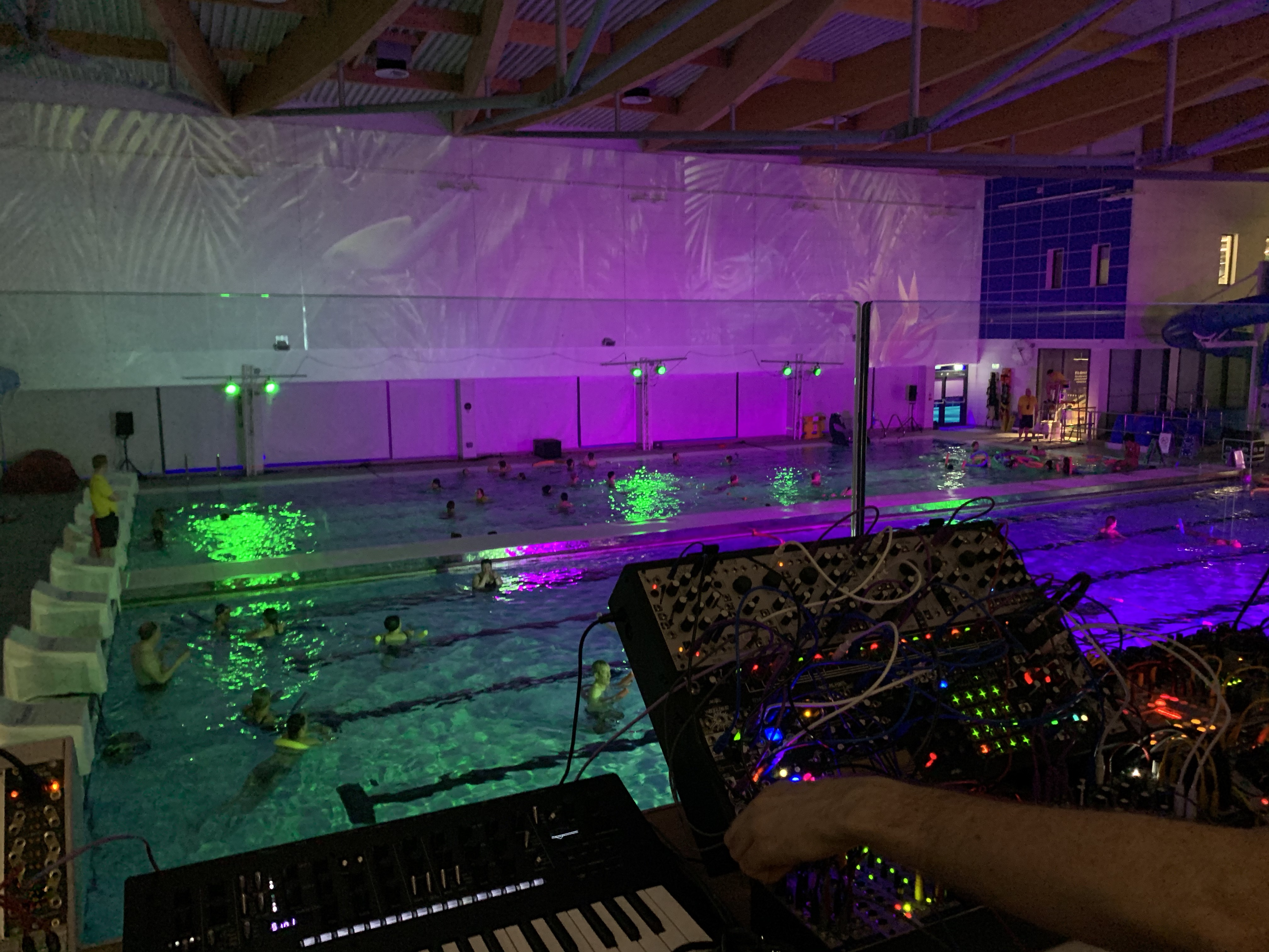 Two synthesisers being played pool side in a neon illuminated swimming pool.
