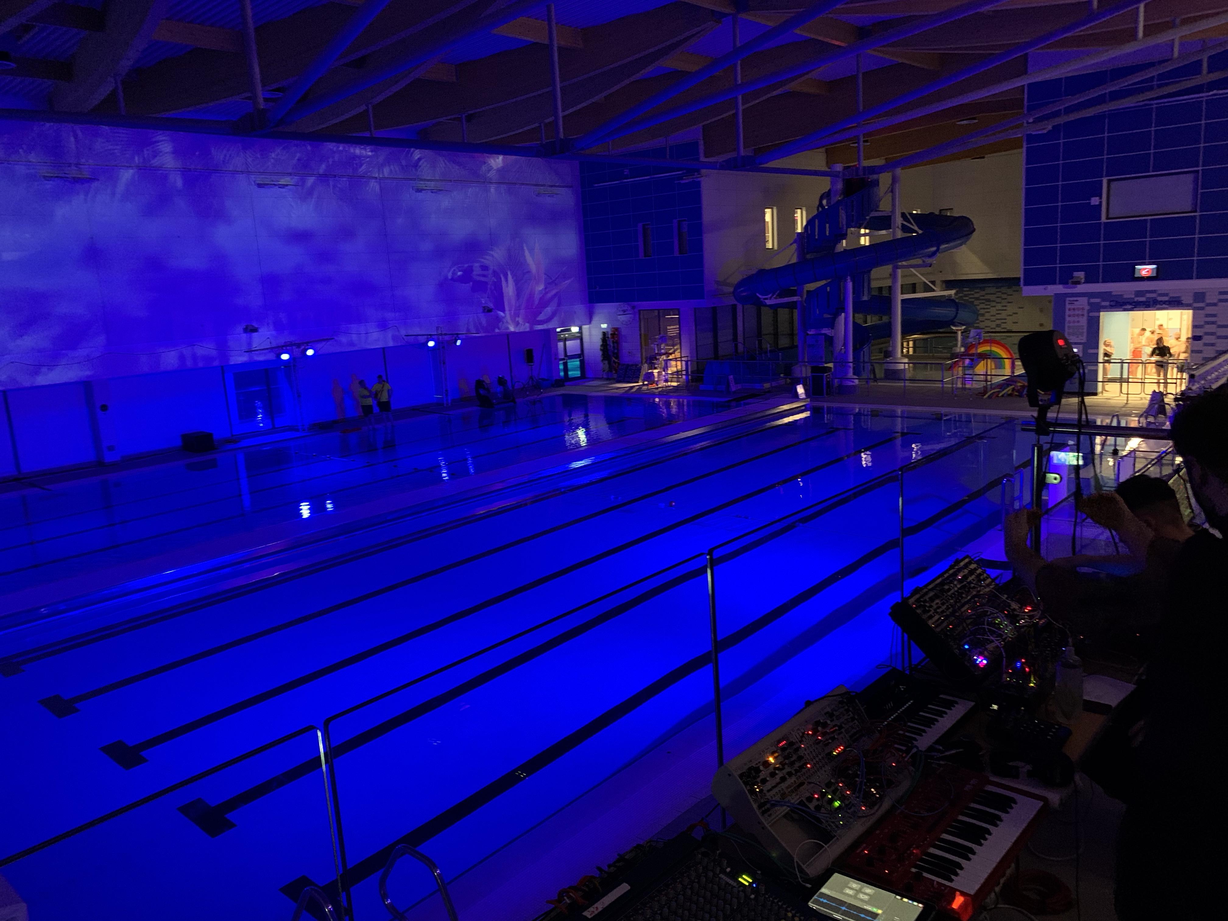 Swimming pool at night with purple lighting